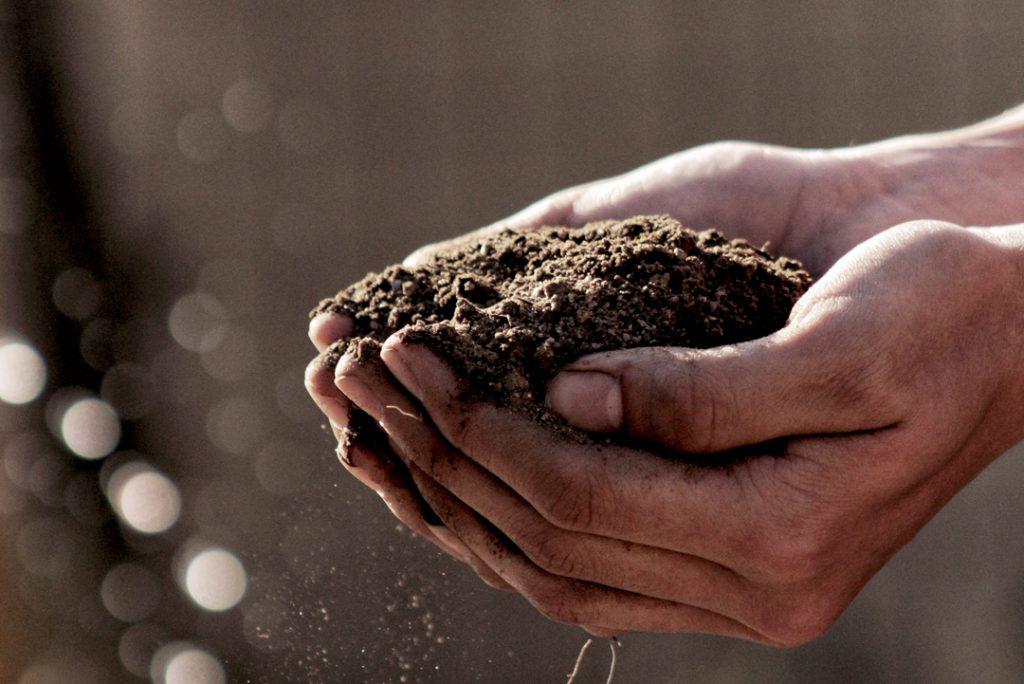 Image: hands holding soil; Source: Gabriel Jimenez, Unsplash