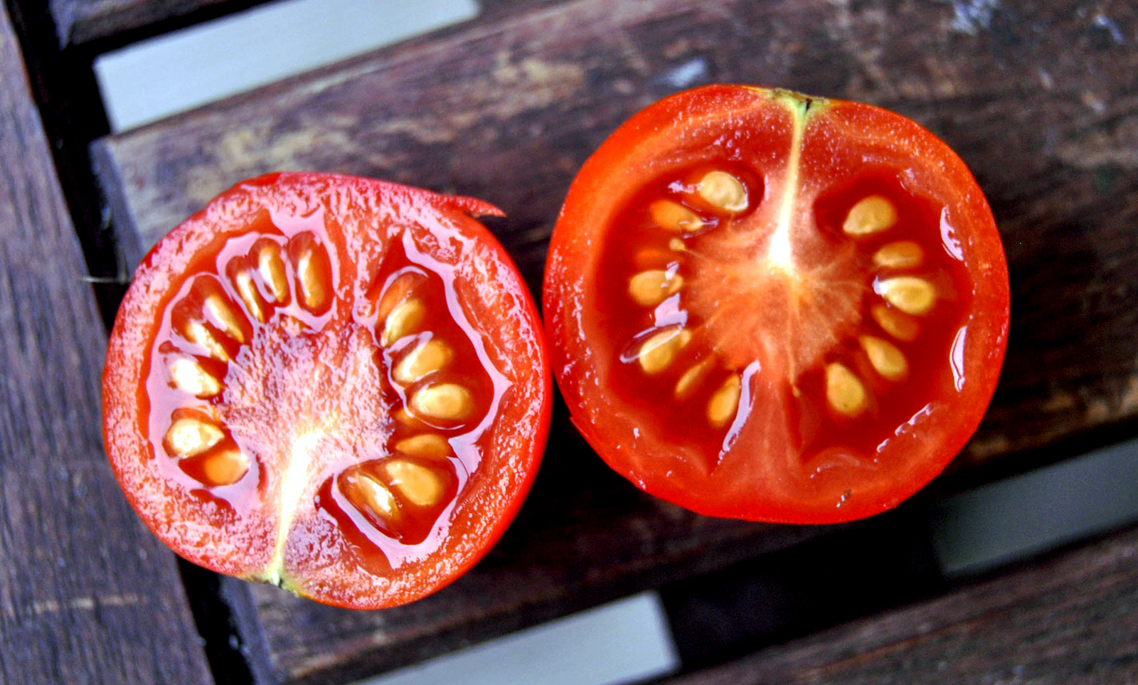 seed saving getting something for nothing image of two halves of a tomato showing the seeds, on a background of wood